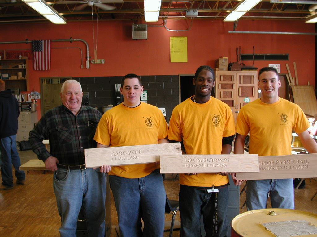 BOCES students holding hand-carved signs